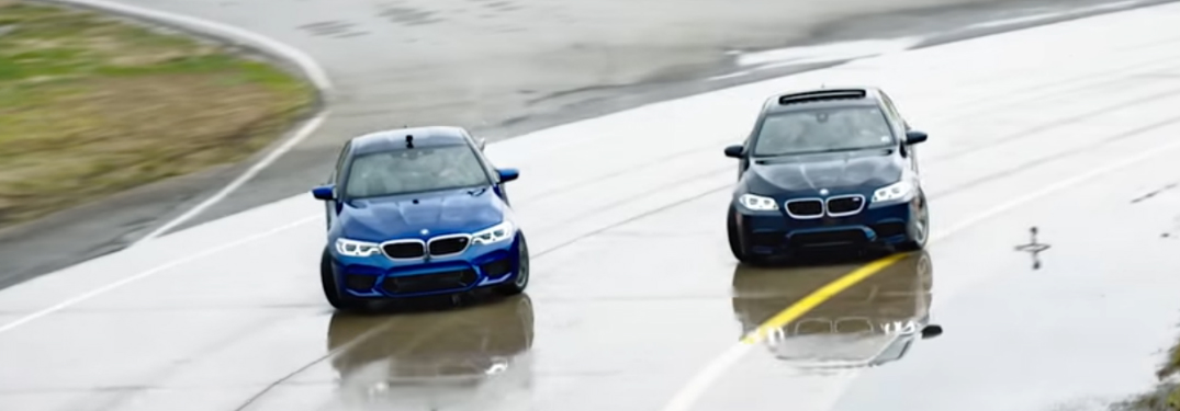 Two BMW M5 Vehicles Drifting on a Wet Race Track