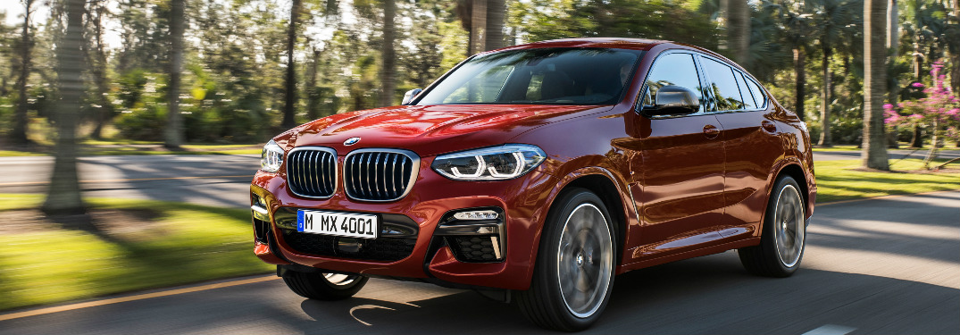 Red 2019 BMW X4 Driving by a Park