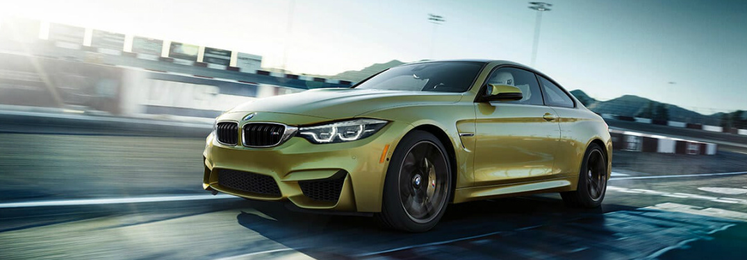Yellow 2018 BMW M4 Driving on a Racetrack