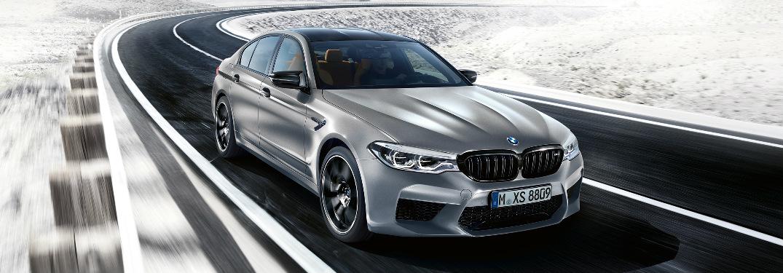 Silver 2019 BMW M5 Competition Sedan Driving Through a Snowy Landscape
