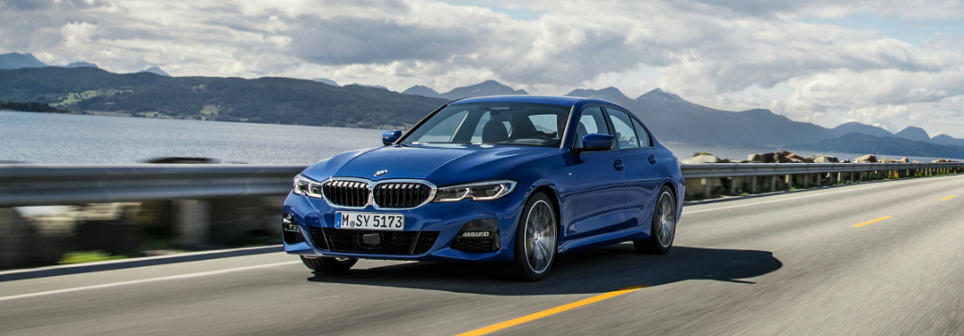 Blue 2019 BMW 3 Series driving over a bridge