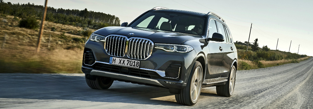 Front view of a grey 2019 BMW X7 driving on a gravel road