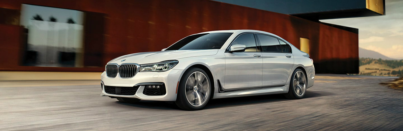 White 2019 BMW 7 Series driving by a large building