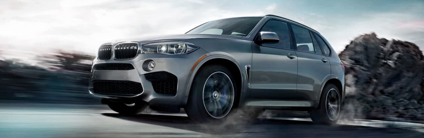 Grey 2019 BMW X5 M driving on a gravel road
