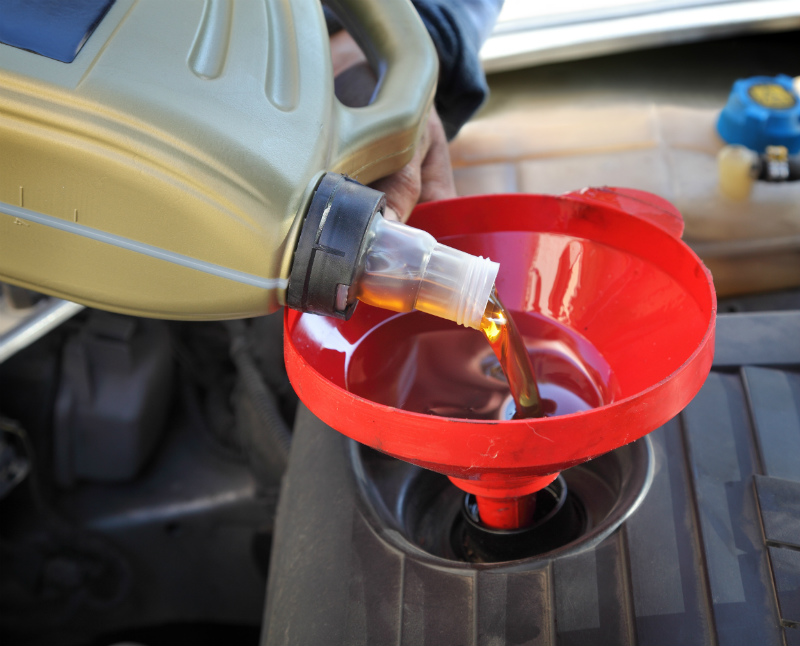 Automotive oil pouring into a funnel above an engine