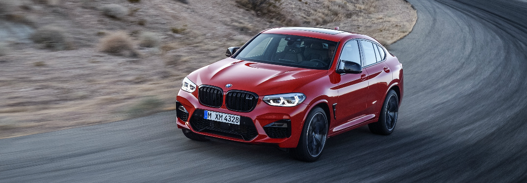 Orange 2020 BMW X4 M driving on a curvy road
