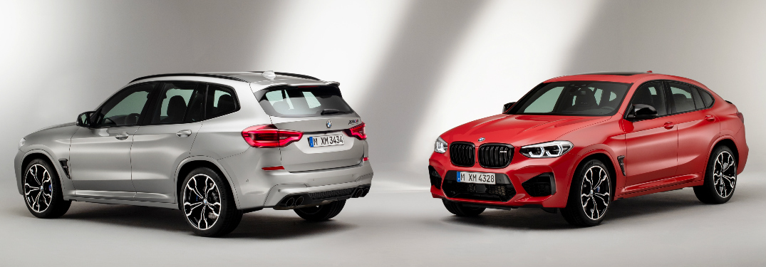 Rear view of silver 2020 BMW X3 M and front view of orange 2020 BMW X4 M
