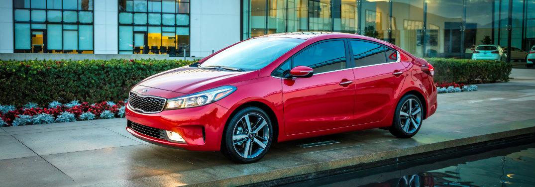 red 2018 kia forte parked next to high-tech building and pool