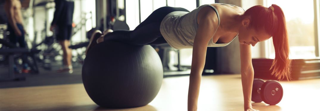 young woman doing push up using exercise ball