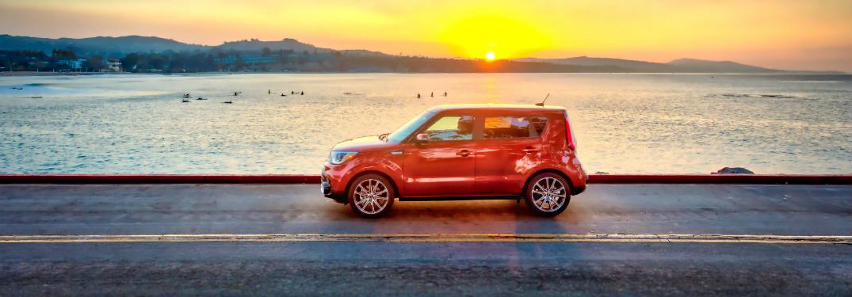 orange 2018 kia soul driving alongside coastal road at sunset