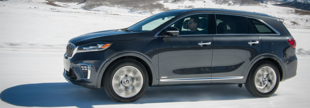 blue 2019 kia sorento driving on snowy trail with mountains behind it