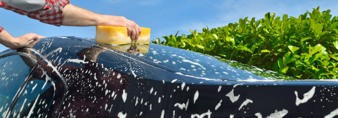 man wiping soap off exterior of car with yellow sponge outside