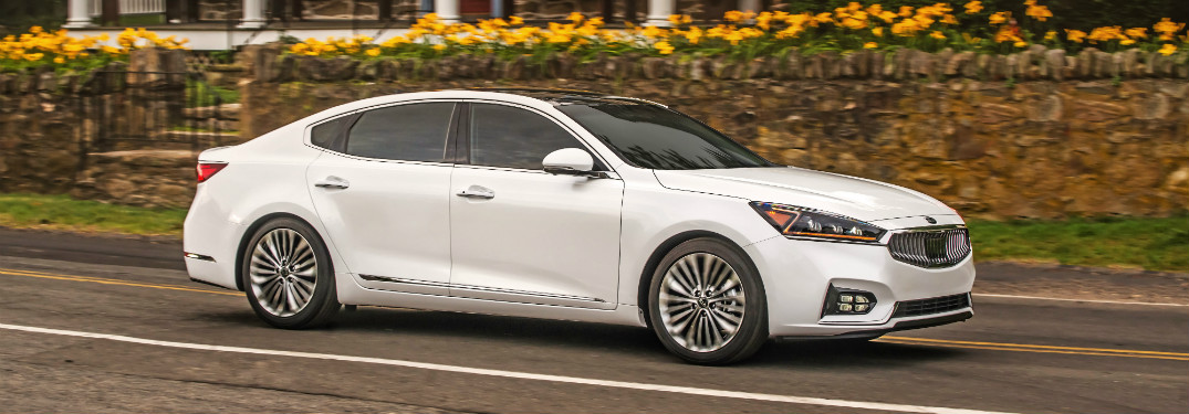 white 2018 kia cadenza driving on road in front of brick house