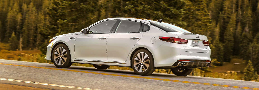 side view of white 2018 kia optima driving on forest road