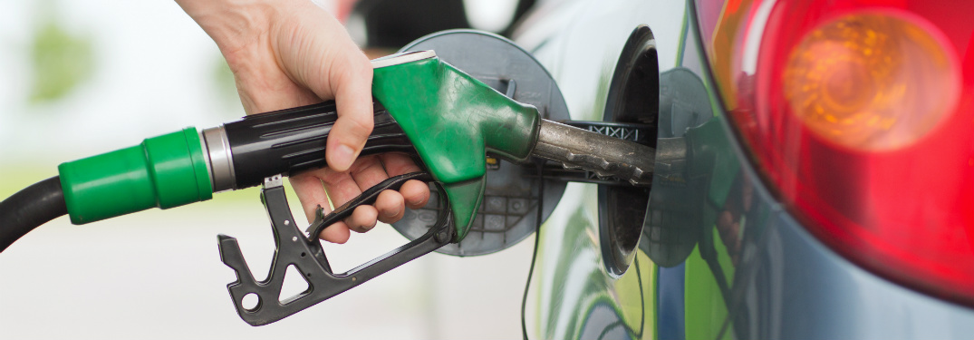 close up of hand holding gas station pump filling up gas tank of car