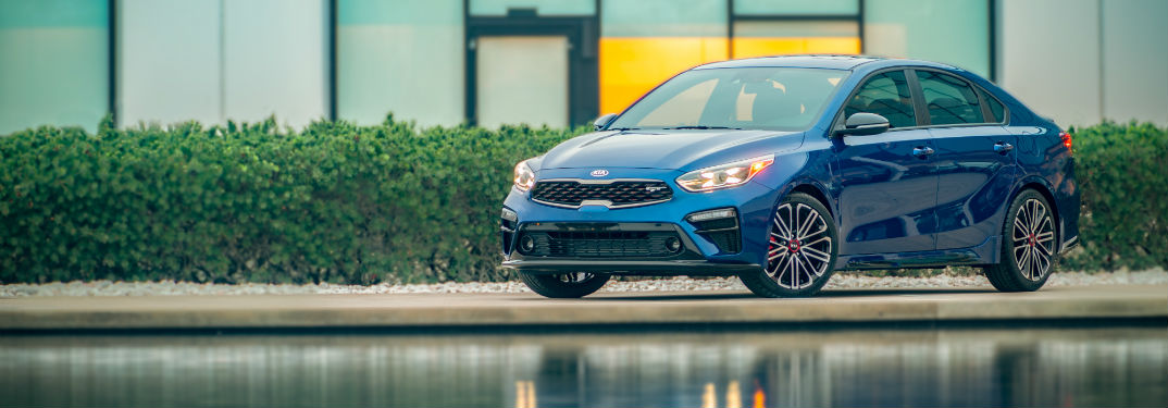 The Sporty 2020 Kia Forte GT with image of the 2020 Kia Forte GT parked by a building and some water