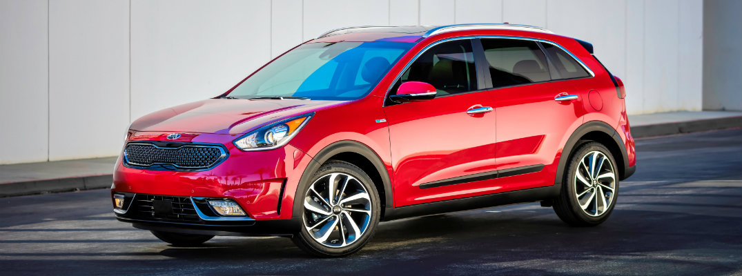 2019 Kia Niro exterior shot with runway red paint color parked next to a white paneled wall