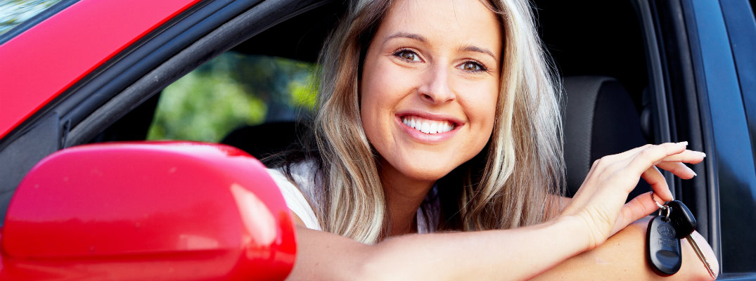 Young blond driver holding the keys to a red Toyota car