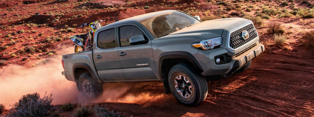 Gray 2018 Toyota Tacoma driving on rough terrain