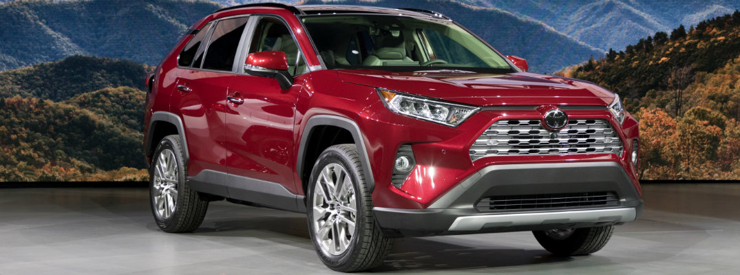 Red 2019 Toyota RAV4 set in front of mountain scene at an auto show