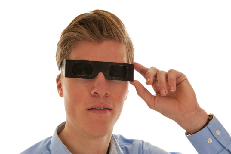 young man wearing solar eclipse glasses