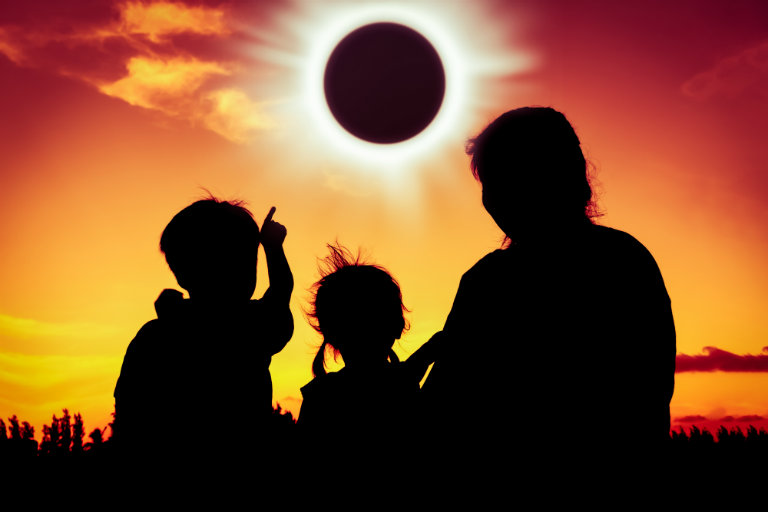 parent and children viewing a total solar eclipse