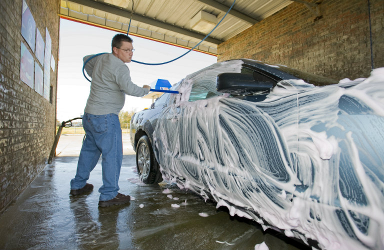 man washing a car in a self-serve car wash location