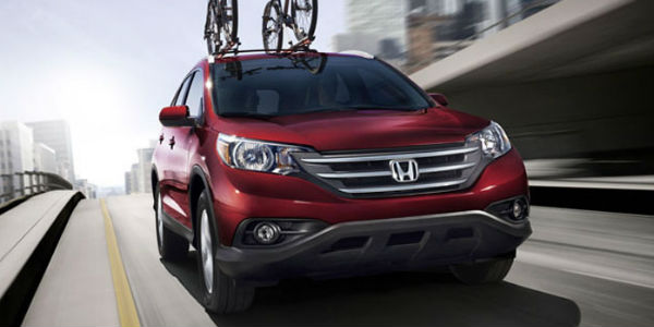 Red 2014 Honda CR-V with Rooftop Bike Rack on City Street