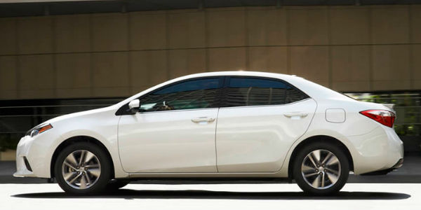 White 2015 Toyota Corolla Side Exterior in Front of Brick Building