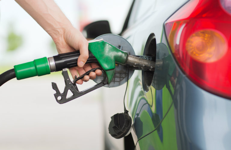green gas pump fueling a car with a hand