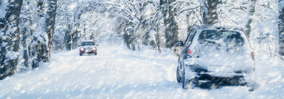 two cars driving down a very snowy, tree-lined road