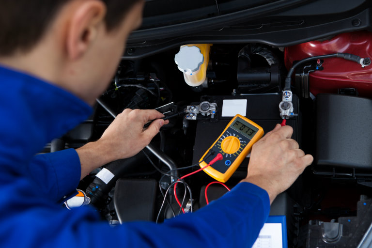 mechanic checking the charge on a car battery