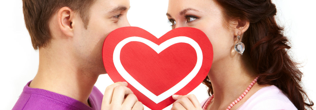 man and a woman holding a paper heart up to cover their mouths