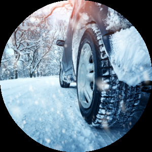 close look at the wheel of a car driving in snow