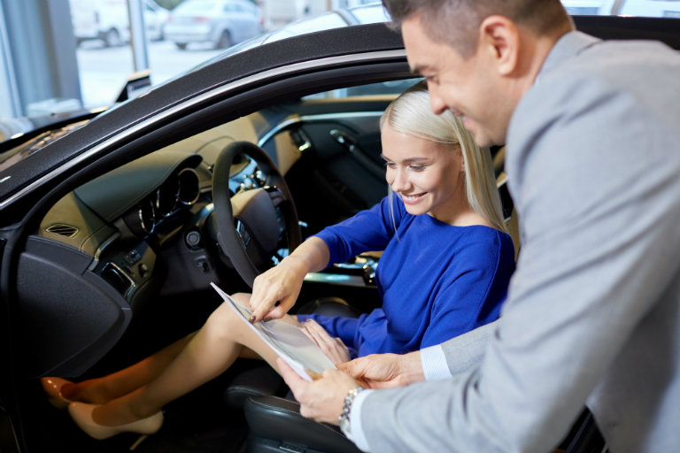 A blonde woman in a blue dress sits in the driver's seat of a car as a salesman helps her check some figures on a form. They are both very happy.