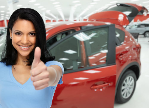 woman giving the camera a thumbs up, red car in the background