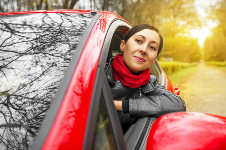 woman driving in a red car, her head out of the window