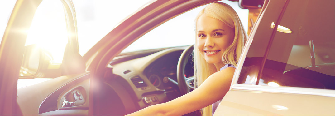 girl smiling in a car holding the door open