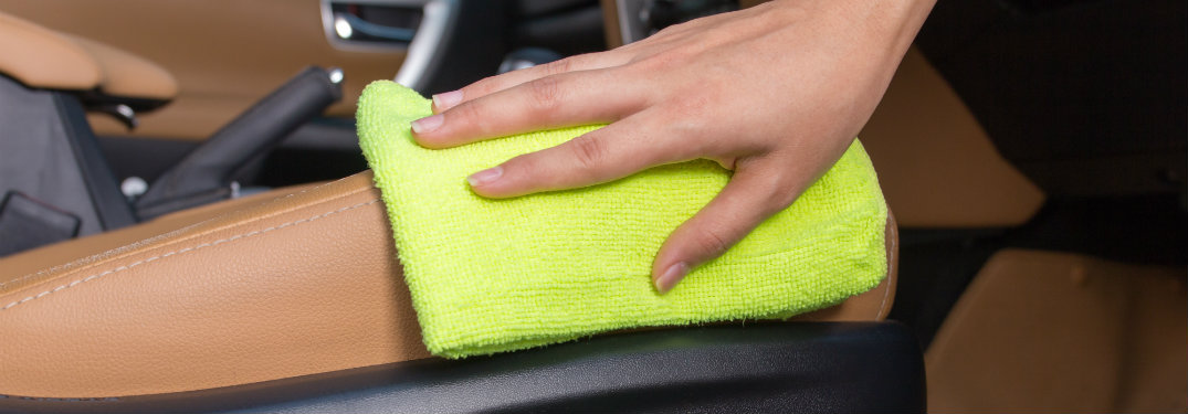 person scrubbing a car's central console with a yellow cloth