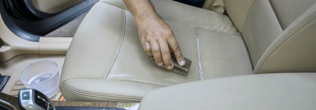 person scrubbing the seat of a car, only the hand visible