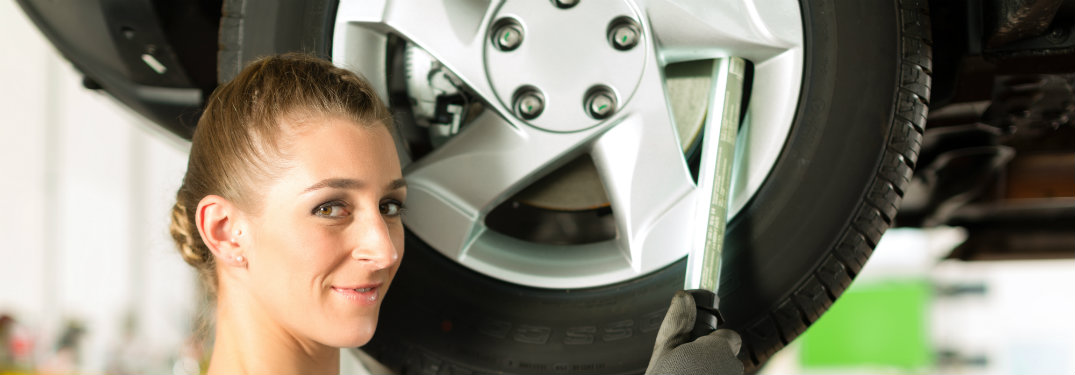 female mechanic with her face by a wheel (car on a lift)