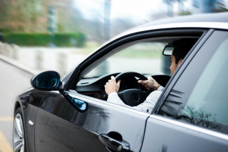 side view of man driving dark car