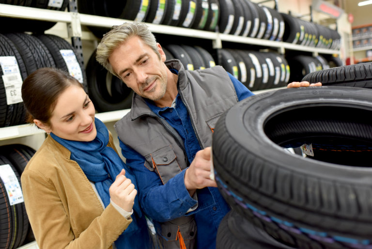couple examining a tire to see if it is right for them