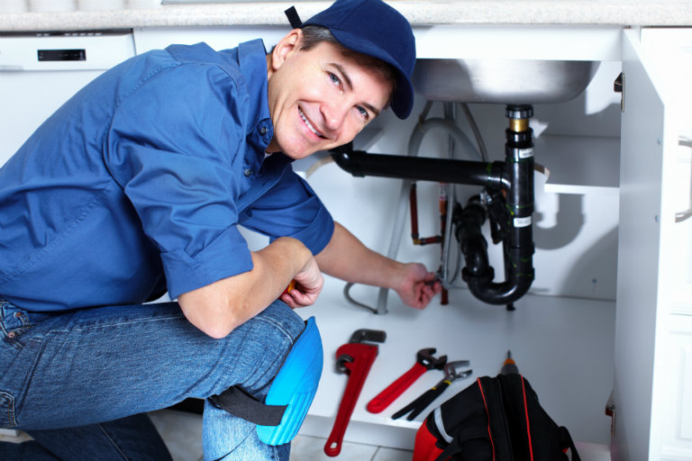 plumber fixing something under a sink and happy about it