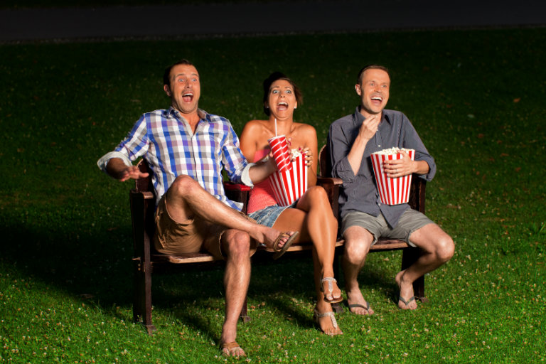 three people watching something, eating popcorn, and showing a big reaction