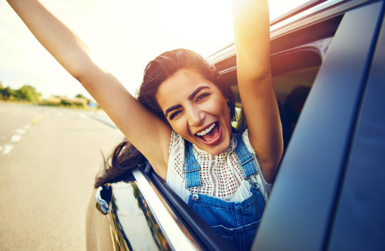 happy woman in car with arms up