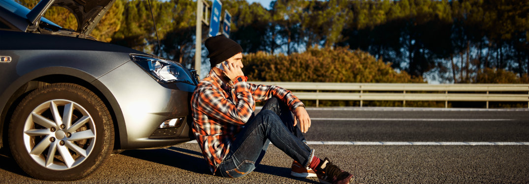 young man with a broken car calling someone