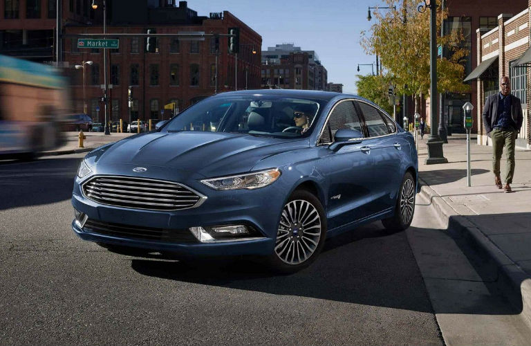 Blue 2018 Ford Fusion pulling away from city curb