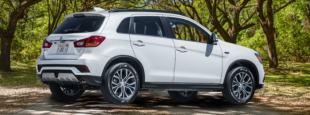 White 2018 Mitsubishi Outlander Sport parked in front of trees in forest