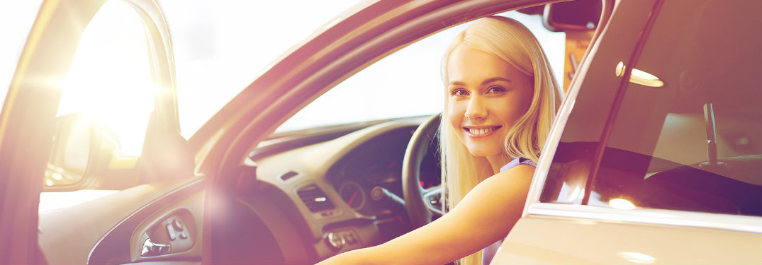 young woman smiling from a car